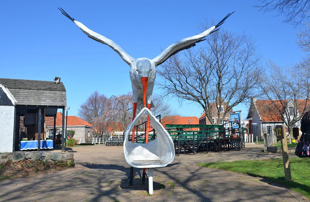 Photo of a giant stork carrying a sack for silly photos with Dutch style buildings in the background