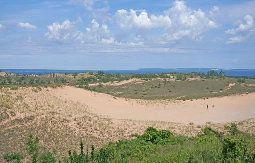 Sand dunes and scrub grass with Lake Michigan and small islands in the far background