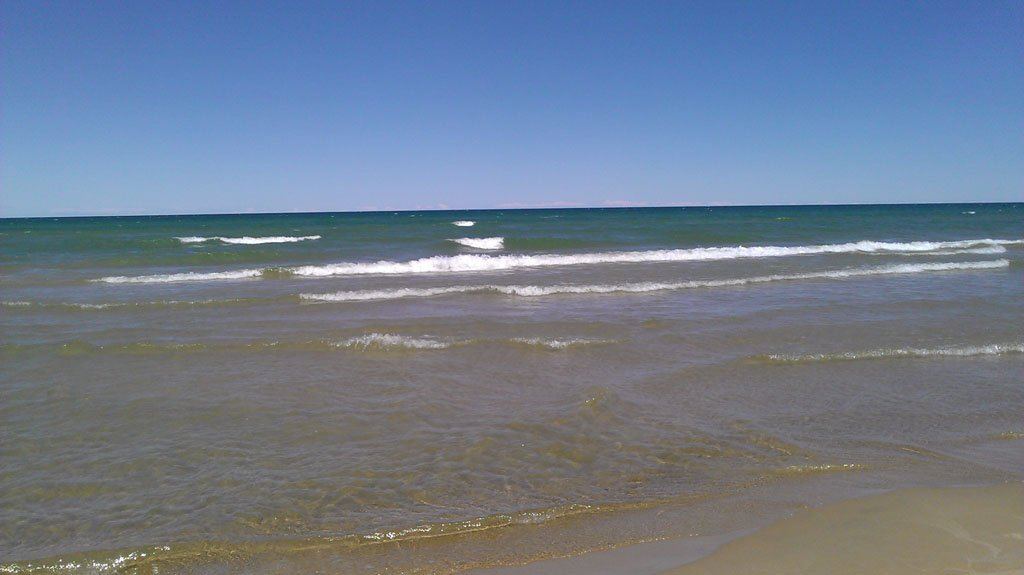 Waves breaking on a sandy beach under bright blue skies during summer in Michigan