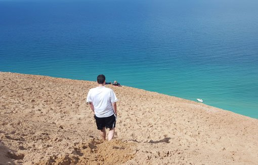 White man walking on a tall sand dune with the turquoise waters of Lake Michigan far below