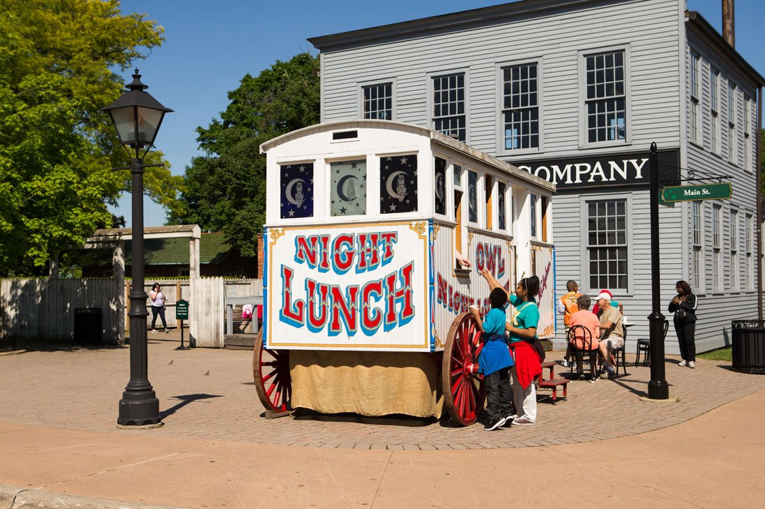 """Old timey food wagon with """"Night Lunch"""" painted on it and visitors waiting to purchase food"""