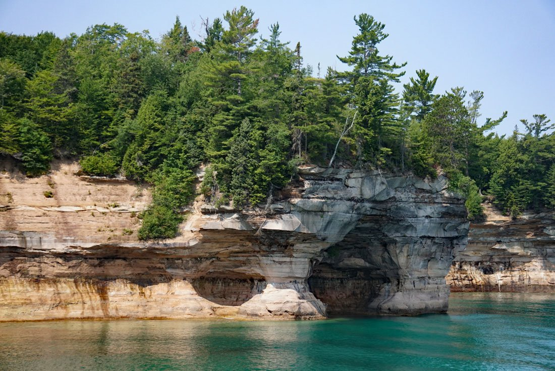 Colorful cliffs with sea caves at the base and green foliage on top in Pictured Rocks National Lakeshore