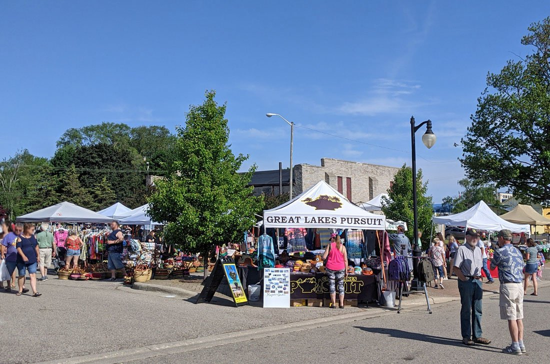 Shoppers brows tents advertising antiques and food items on a sunny summer morning at the Port Austin Farmers Market