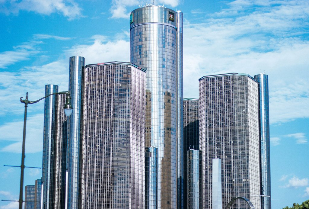 Tall, cylindrical towers of the Renaissance Center in Detroit with bright, partly-cloudy skies in the background