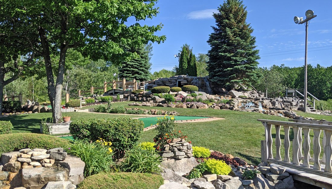 Photo of a mini golf course with green grass and a large artificial waterfall in the background