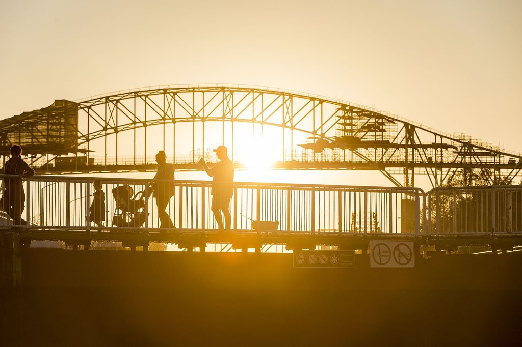 Pedestrians on a bridge with the sunsetting behind them at the Soo Locks