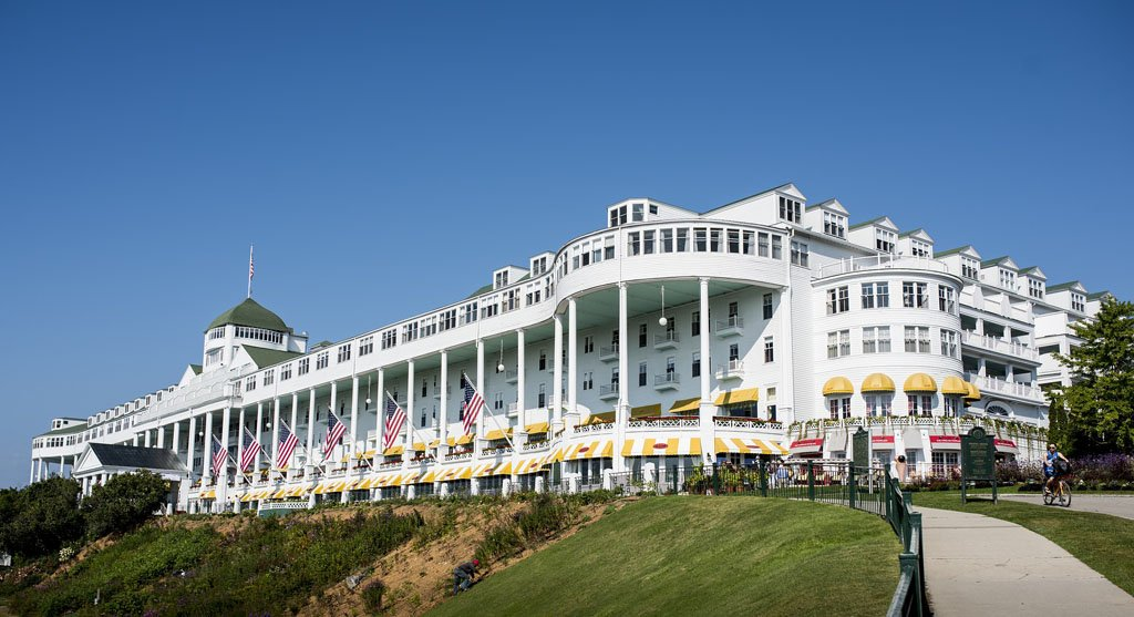 The Grand Hotel, a massive white Victorian hotel on Mackinac Island with a long covered front porch