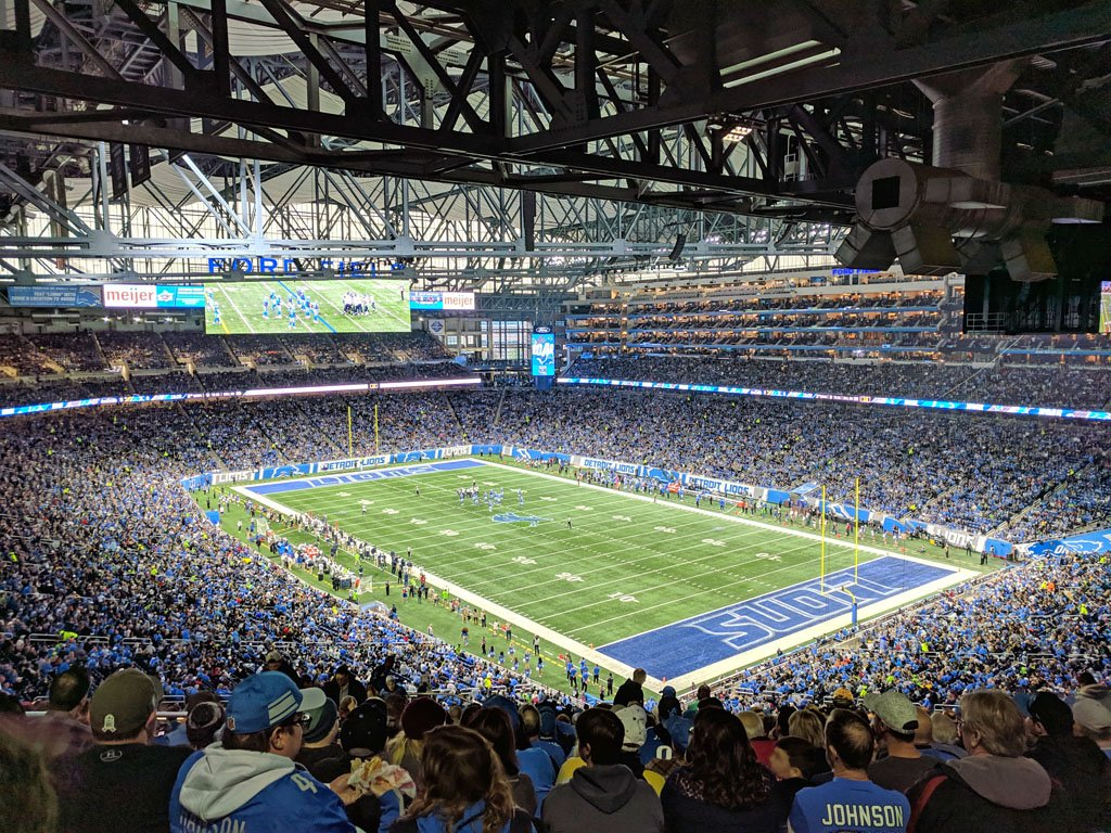 Photo of the field inside Ford Field, with stands packed with Detroit Lions fans and players on the field