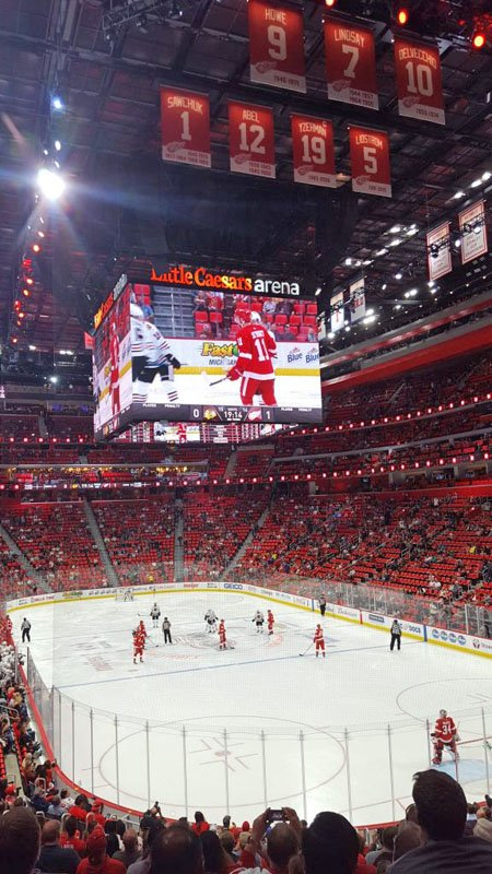 Photo of the ice inside Little Caesars Arena with the stands full of Red Wings fans, players in action on the ice, and banners of retired jerseys in the rafters