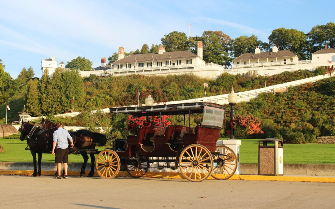 Photo of a horse-drawn carriage parked below Fort Mackinac, two of the top things to do on Mackinac Island