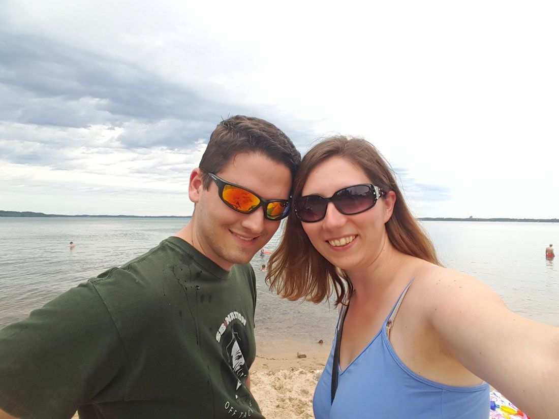 White man and woman, each wearing sunglasses, smile for the camera in a selfie on one of the Traverse City beaches with water stretching out to the horizon