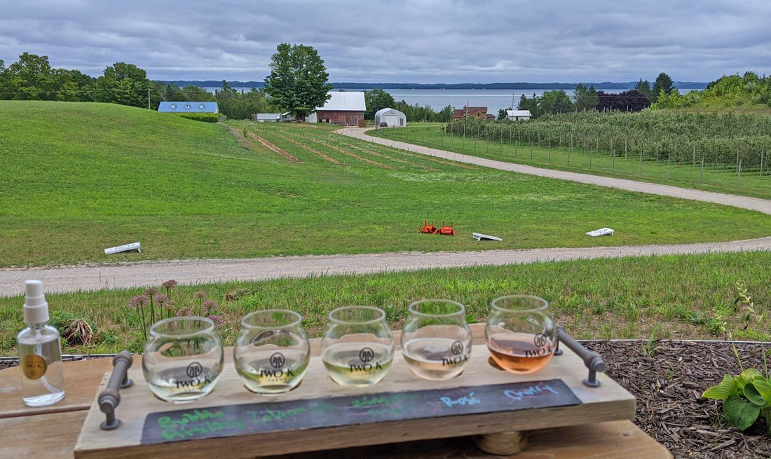 Photo of a flight of small wine glasses taken from a vantage point overlooking a wide green lawn with Grand Traverse Bay in the background. Photo was taken at one of the Traverse City area wineries.