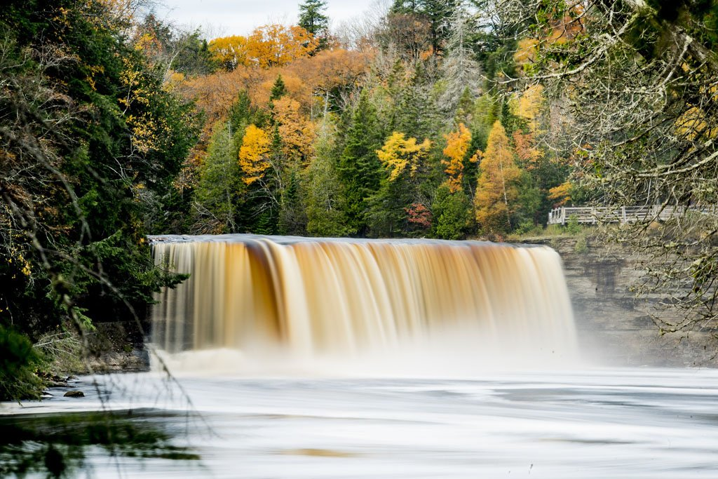 Tahquamenon Upper Falls, a tall, wide waterfall with brownish water and colorful fall foliage in the background