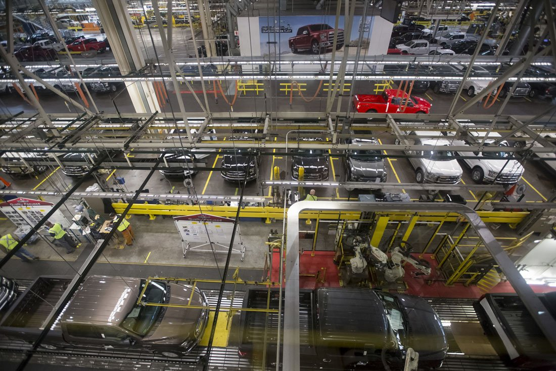 Overhead view of the assembly floor where machinery and equipment surround trucks being built on the Ford Rouge Factory Tour