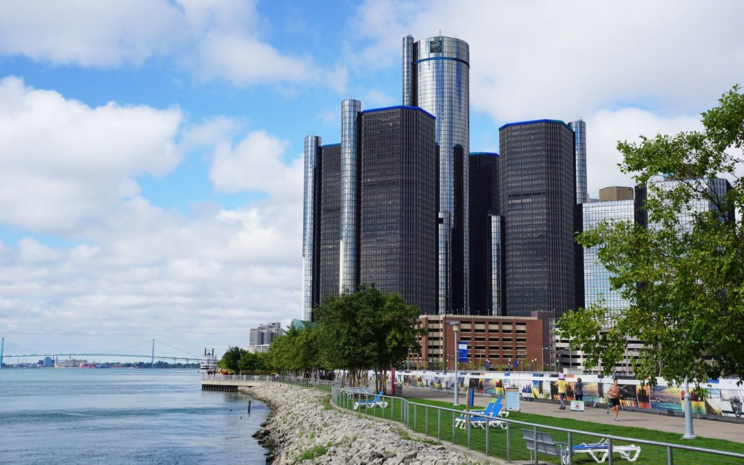 Photo of the Detroit riverfront with the Detroit River on the left and the tall, cylindrical towers of the Renaissance Center on the right with people enjoying the Riverwalk in the foreground