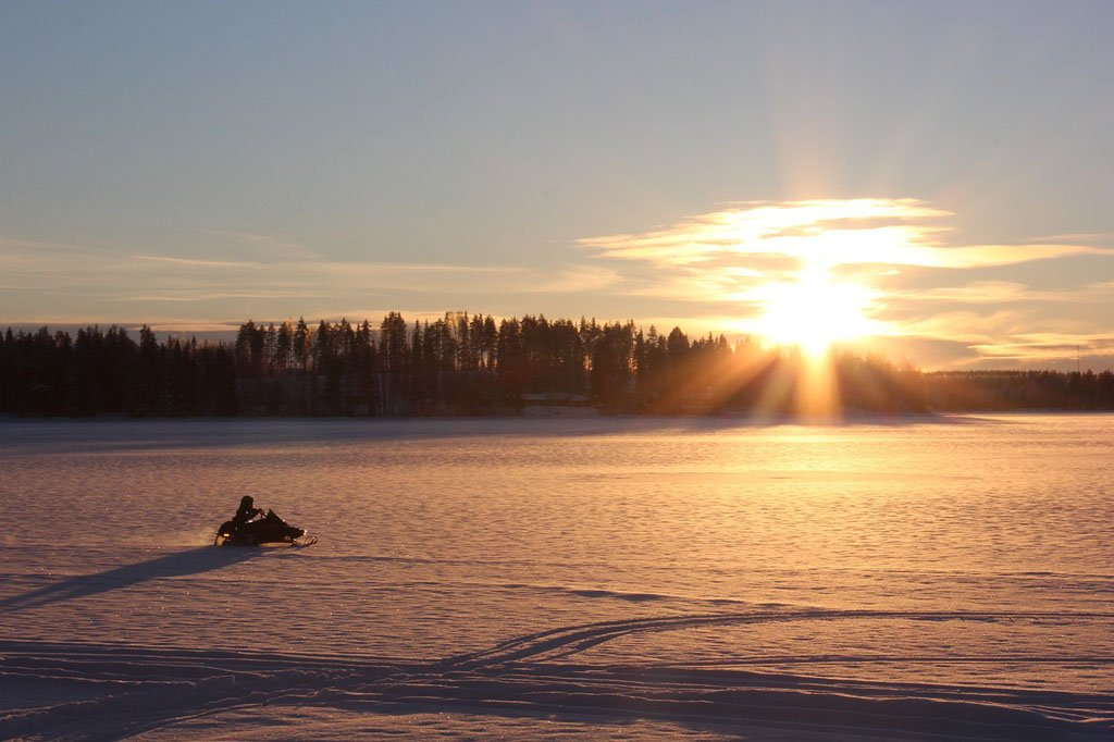 Snowmobiler riding across a flat, snowy expanse as the sun sets behind trees in the background