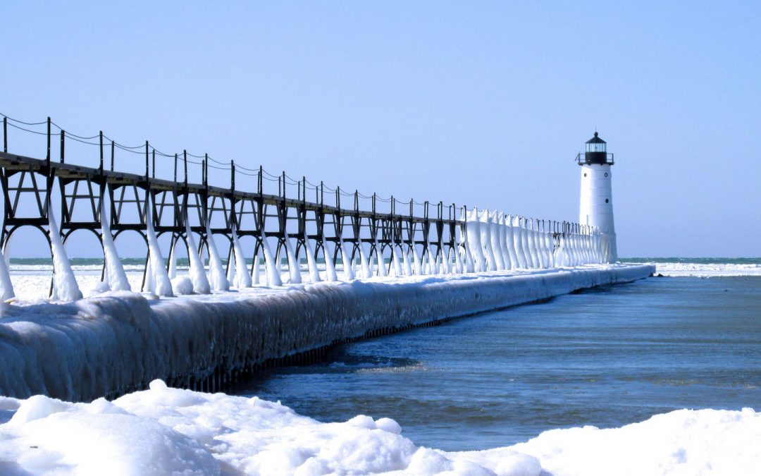 Breakwater with a small lighthouse at the end, coated with ice and snow during winter in Michigan