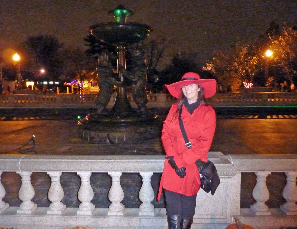 Woman dressed in a red trench coat and wide-brimmed hat posing in front of a dry fountain